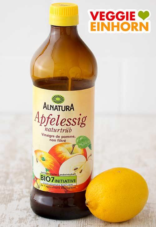 Eine Flasche Apfelessig und eine Zitrone