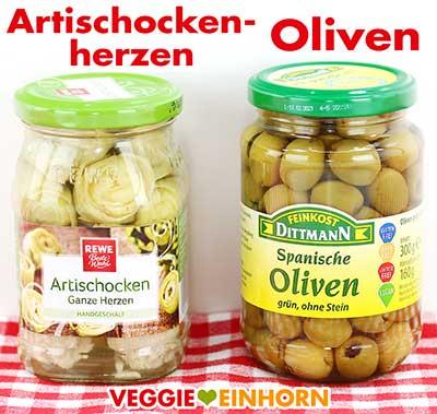 Artischockenherzen und grüne Oliven im Glas