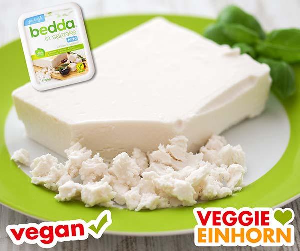 Ein Stück veganer Feta und zerkrümelter Feta auf einem Teller