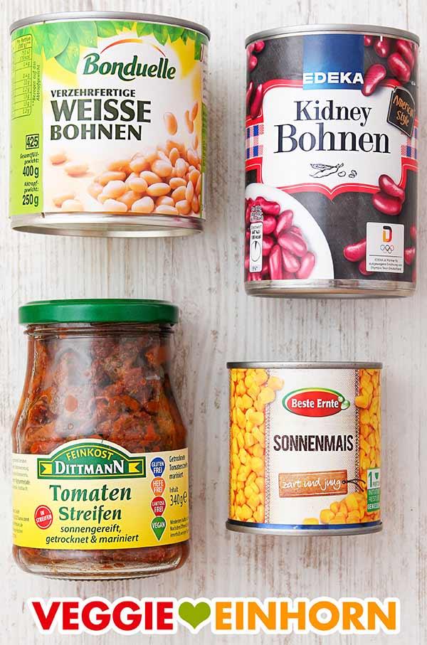 Konservendosen mit weißen Bohnen, Kidneybohnen und Mais und ein Glas getrocknete Tomaten in Öl