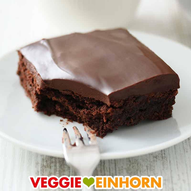 Ein veganer Brownie mit cremiger Schokoglasur auf einem Teller