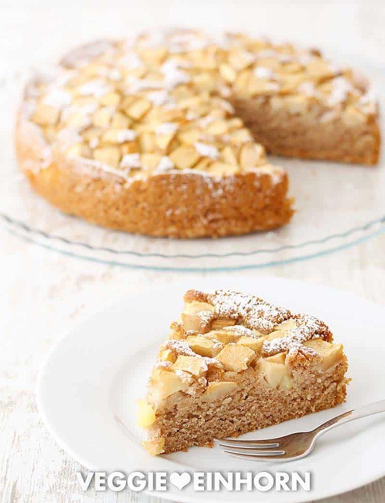 Veganer Apfelkuchen auf einer Kuchenplatte und ein Stück Kuchen auf einem Teller
