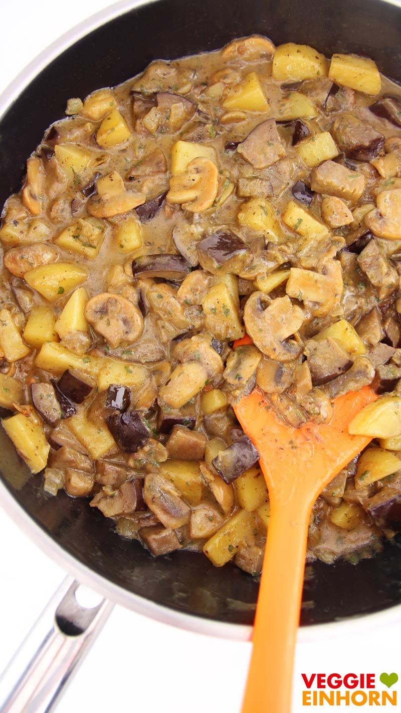 Veganes Curry mit Auberginen, Champignons und Kartoffeln in der Pfanne