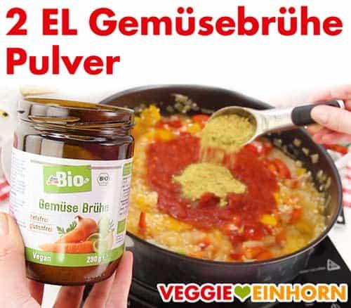Vegane Paella wird gewürzt mit Gemüsebrühe Pulver