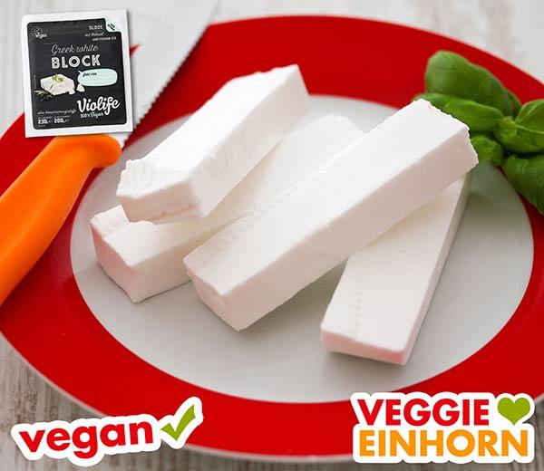 In Scheiben geschnittener veganer Feta Käse auf einem Teller.