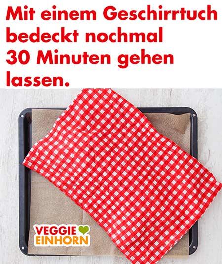 Hefezopf auf dem Backblech mit einem Geschirrtuch bedeckt