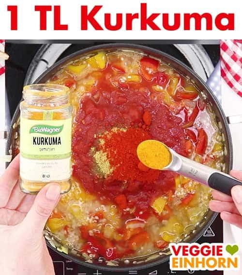 Vegane Paella wird gewürzt mit gemahlenem Kurkuma