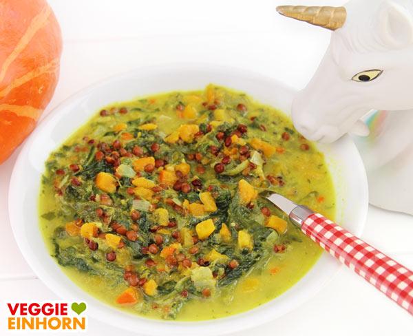 Veganer Linseneintopf mit Kürbis, Spinat und Kokosmilch auf Teller serviert