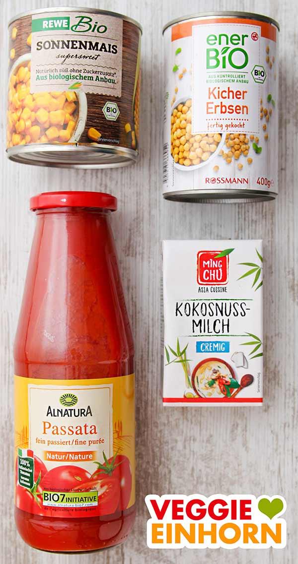 Eine Dose Mais, eine Dose Kichererbsen, eine Flasche passierte Tomaten, ein Tetrapack mit Kokosmilch