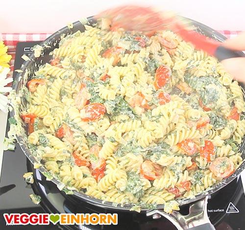 Nudeln mit veganer Frischkäse-Soße, Tomaten und Blattspinat in der Pfanne