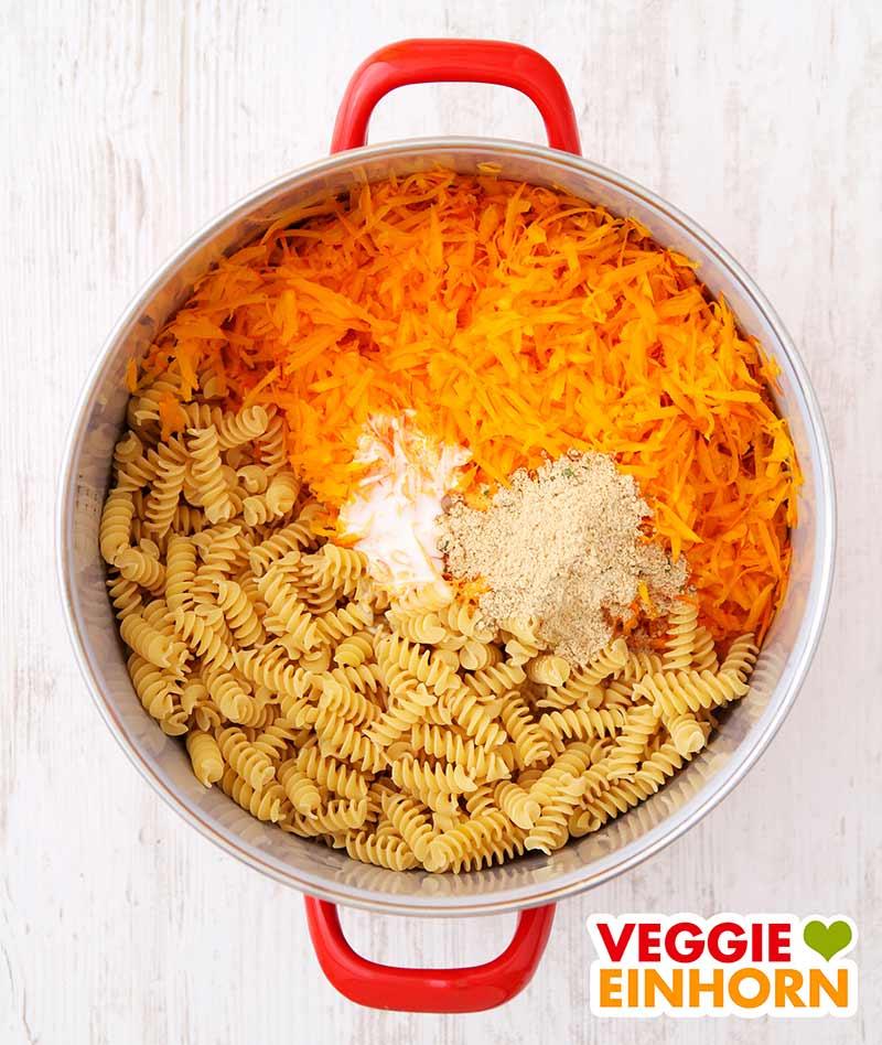 Geraspelter Kürbis, Nudeln, Soja Cuisine und Gemüsebrühe im Topf