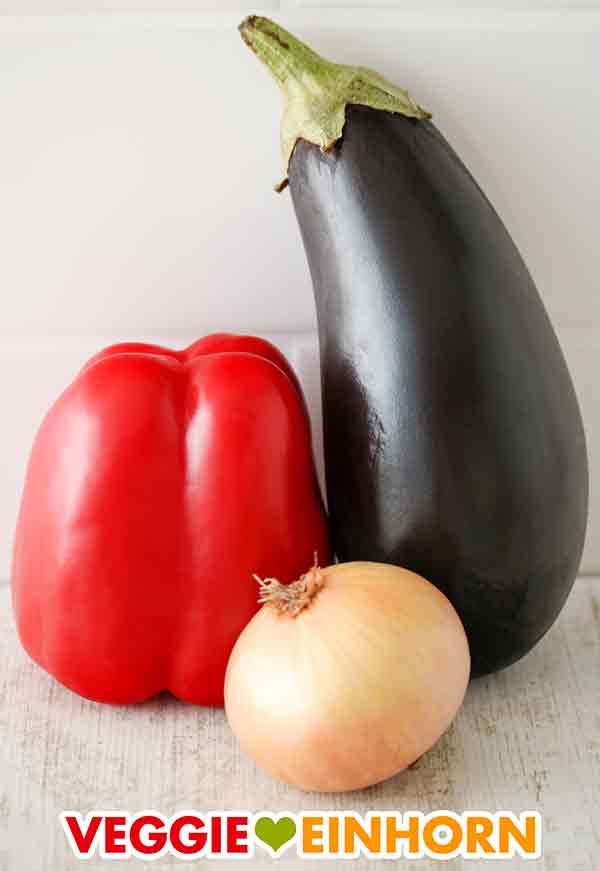 Eine Paprika, eine Aubergine und eine Zwiebel