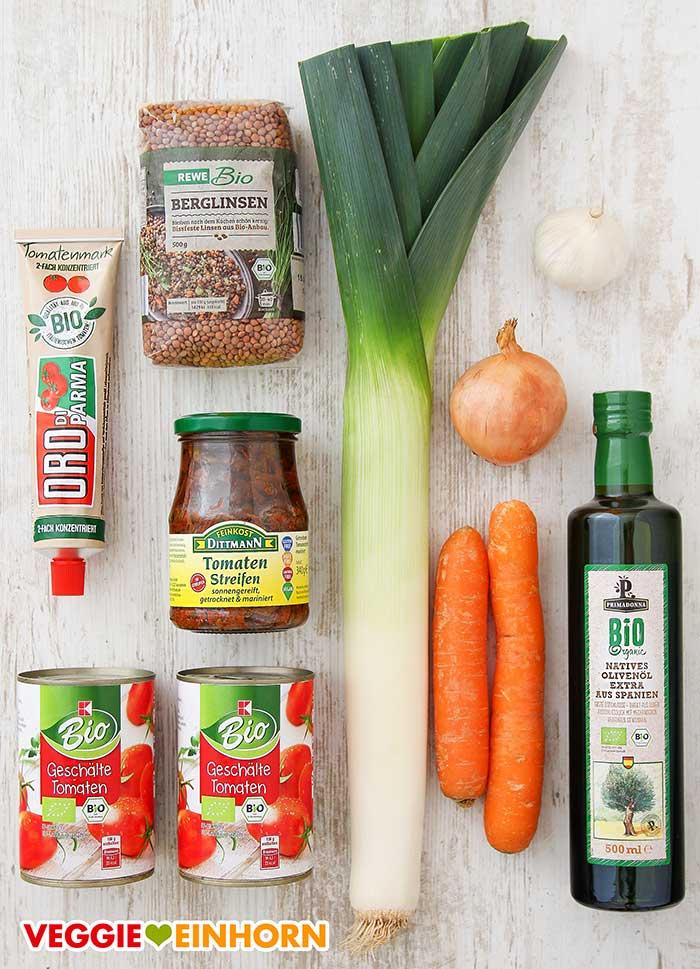 Eine Packung Berglinsen, ein Glas getrocknete Tomaten in Öl, eine Stange Lauch, zwei Möhren und weitere Produkte auf dem Tisch