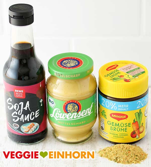 Eine Flasche Sojasauce, ein Glas veganer Senf, ein Glas Gemüsebrühe Pulver