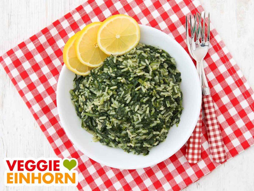 Ein Teller mit Spinatreis und drei Zitronenscheiben