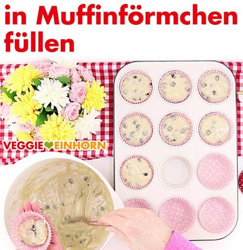 Muffinteig mit frischen Blaubeeren in Papierförmchen füllen