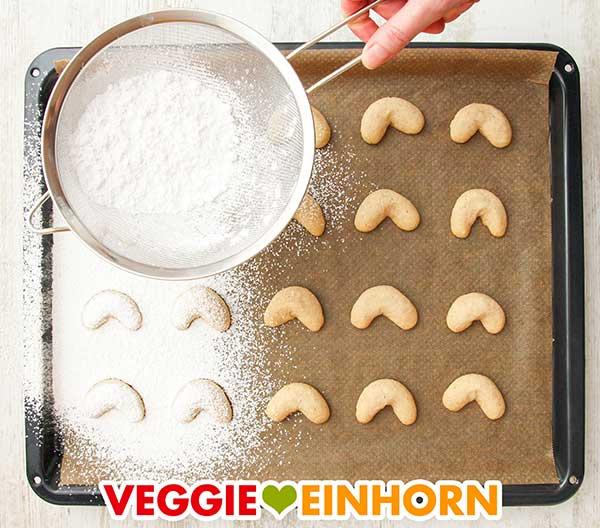 Heiße Vanillekipferl auf dem Backblech werden mit Puderzucker aus einem Sieb bestreut
