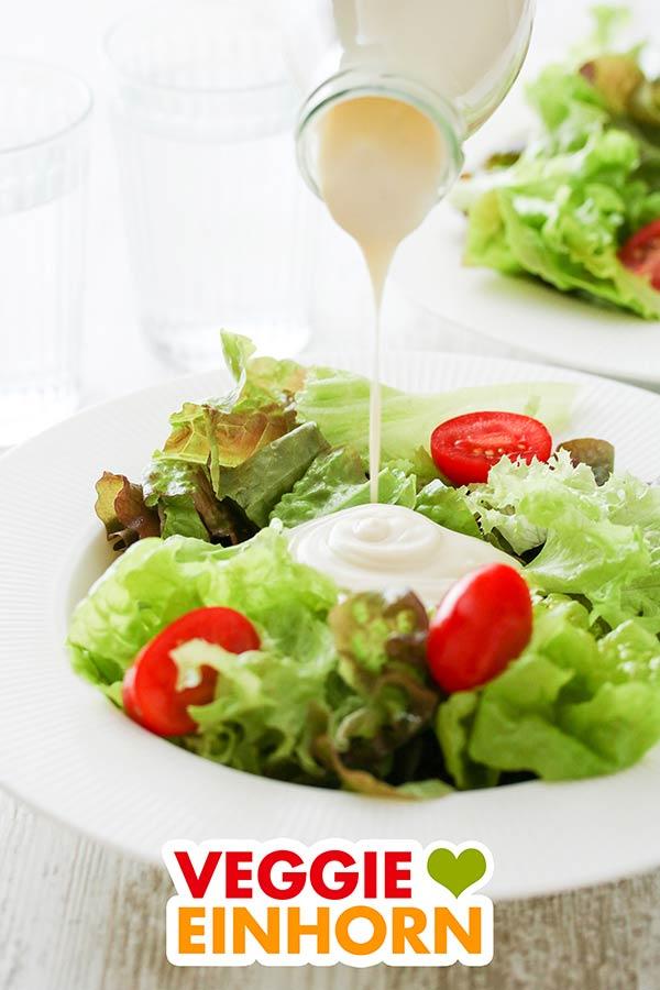 Die cremige Knoblauch-Joghurtsauce wird auf einen Salat gegossen