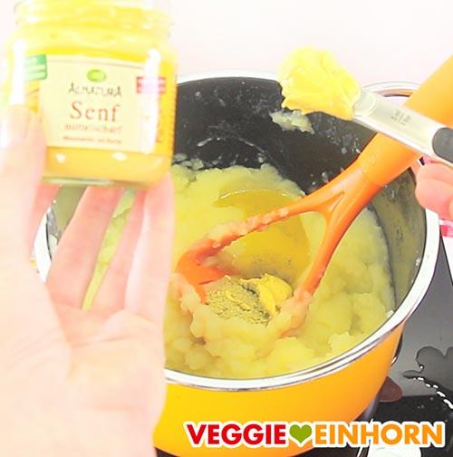 Veganen Senf zum Kartoffelbrei zufügen
