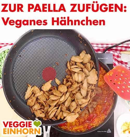 Veganes Hähnchenfilet wird zu Paella zugefügt