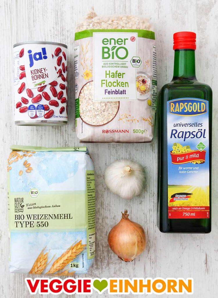 Eine Dose Kidneybohnen, eine Packung Haferflocken, eine Flasche Rapsöl, eine Packung Weizenmehl Type 550, eine Knolle Knoblauch und eine kleine Zwiebel