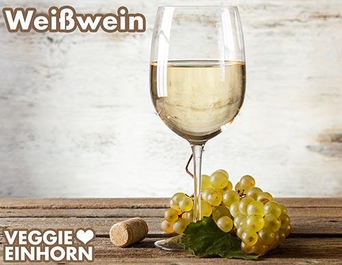 Weißwein in einem Glas und weiße Trauben