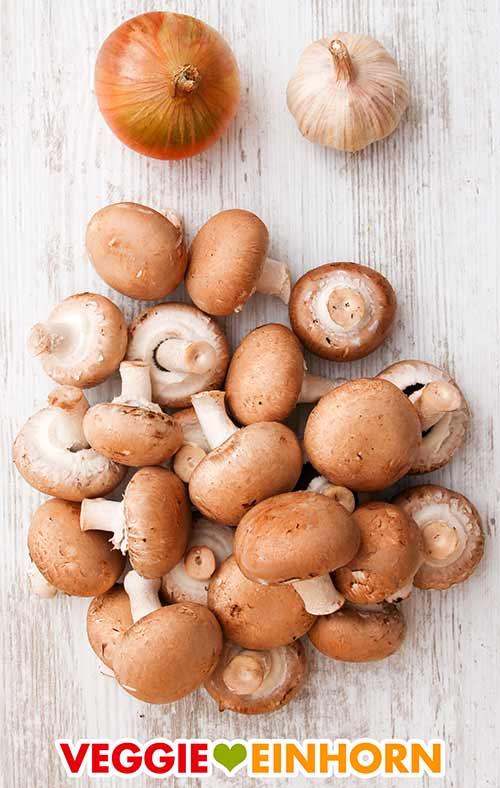 Eine Zwiebel, eine Knoblauchknolle und ein Haufen brauner Champignons