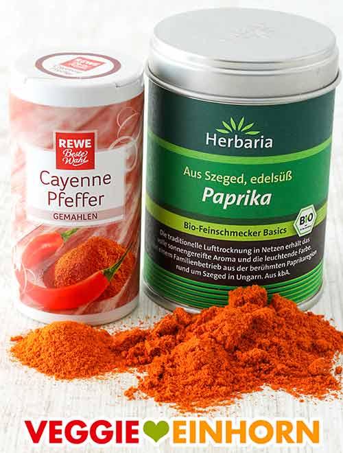 Eine Dose Cayennepfeffer und eine Dose Paprika edelsüß Pulver