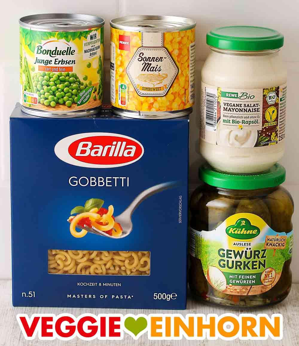 Eine kleine Dose Erbsen, eine kleine Dose Mais, ein Glas vegane Mayonnaise, Nudeln, Gewürzgurken