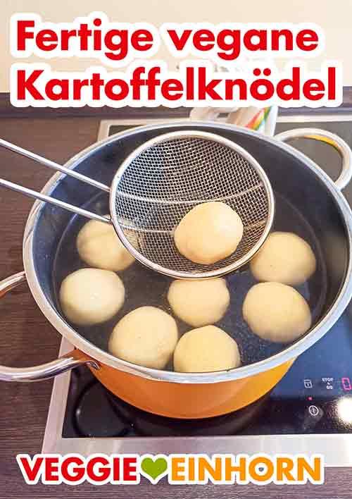 Eine Schaumkelle mit einem fertig gekochten Kartoffelknödel