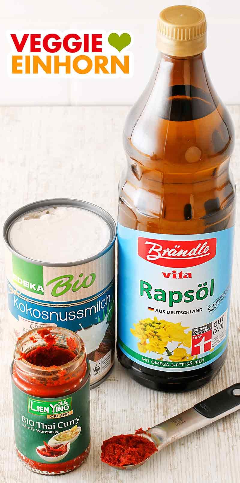 Eine Dose Kokosmilch, eine Flasche Öl und ein Glas rote Thai Curry Paste