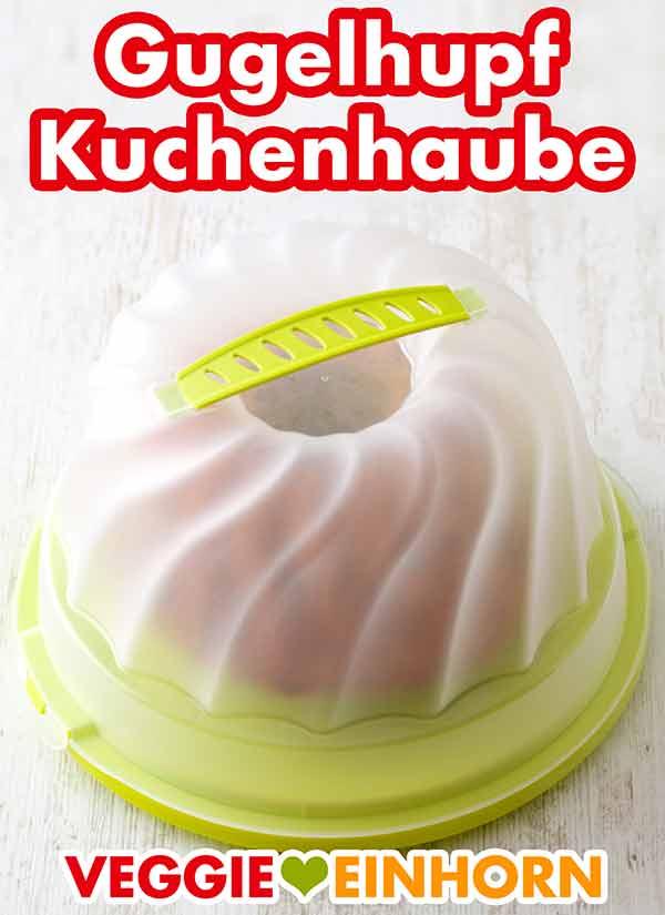 Ein Topfkuchen mit Rosinen unter einer Gugelhupf Kuchenhaube