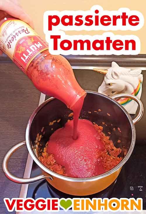 Eine Flasche passierte Tomaten wird in den Topf zugefügt