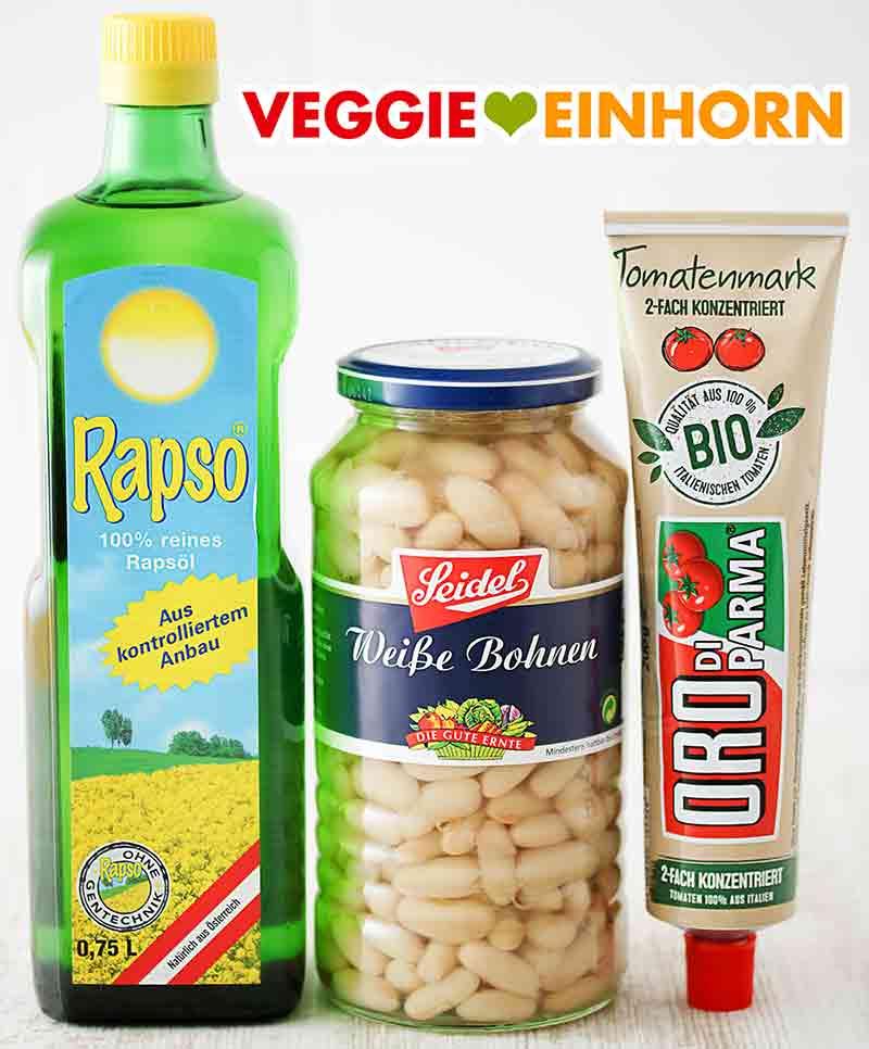 Eine Flasche Rapsöl, ein Glas weiße Bohnen und eine Tube Tomatenmark