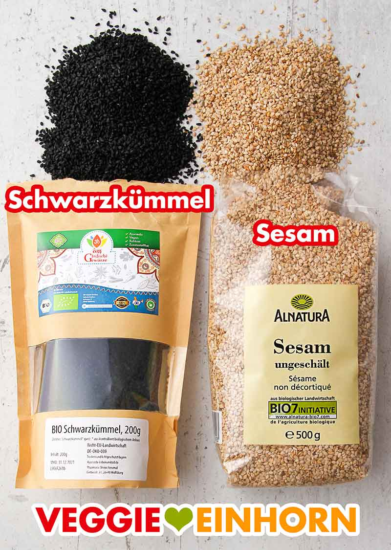 Eine Packung Schwarzkümmel Samen und eine Packung Sesam