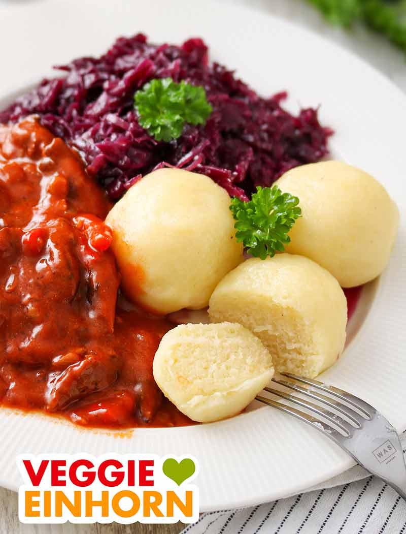Ein Teller mit veganen Kartoffelknödeln, veganem Gulasch und Rotkohl