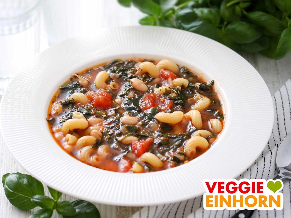 Weiße Bohnensuppe mit Nudeln und Spinat auf einem Teller