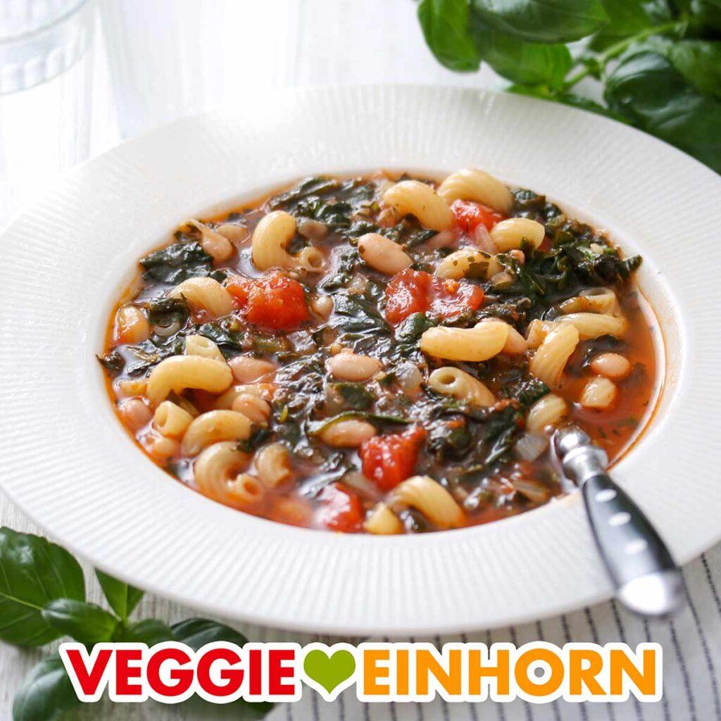 Weiße Bohnensuppe mit Spinat und Nudeln auf einem Teller