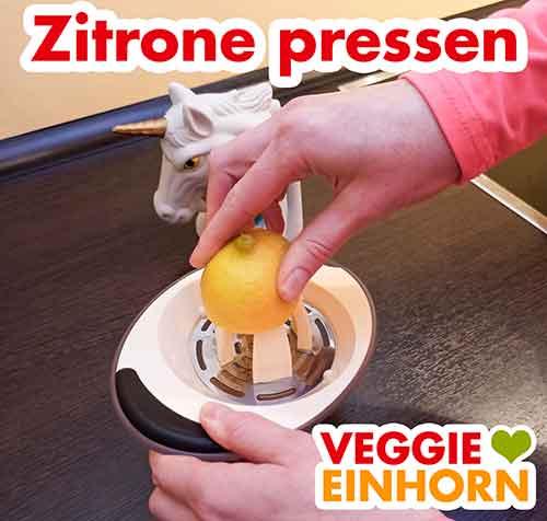 Eine halbe Zitrone wird mit einer Zitruspresse ausgepresst